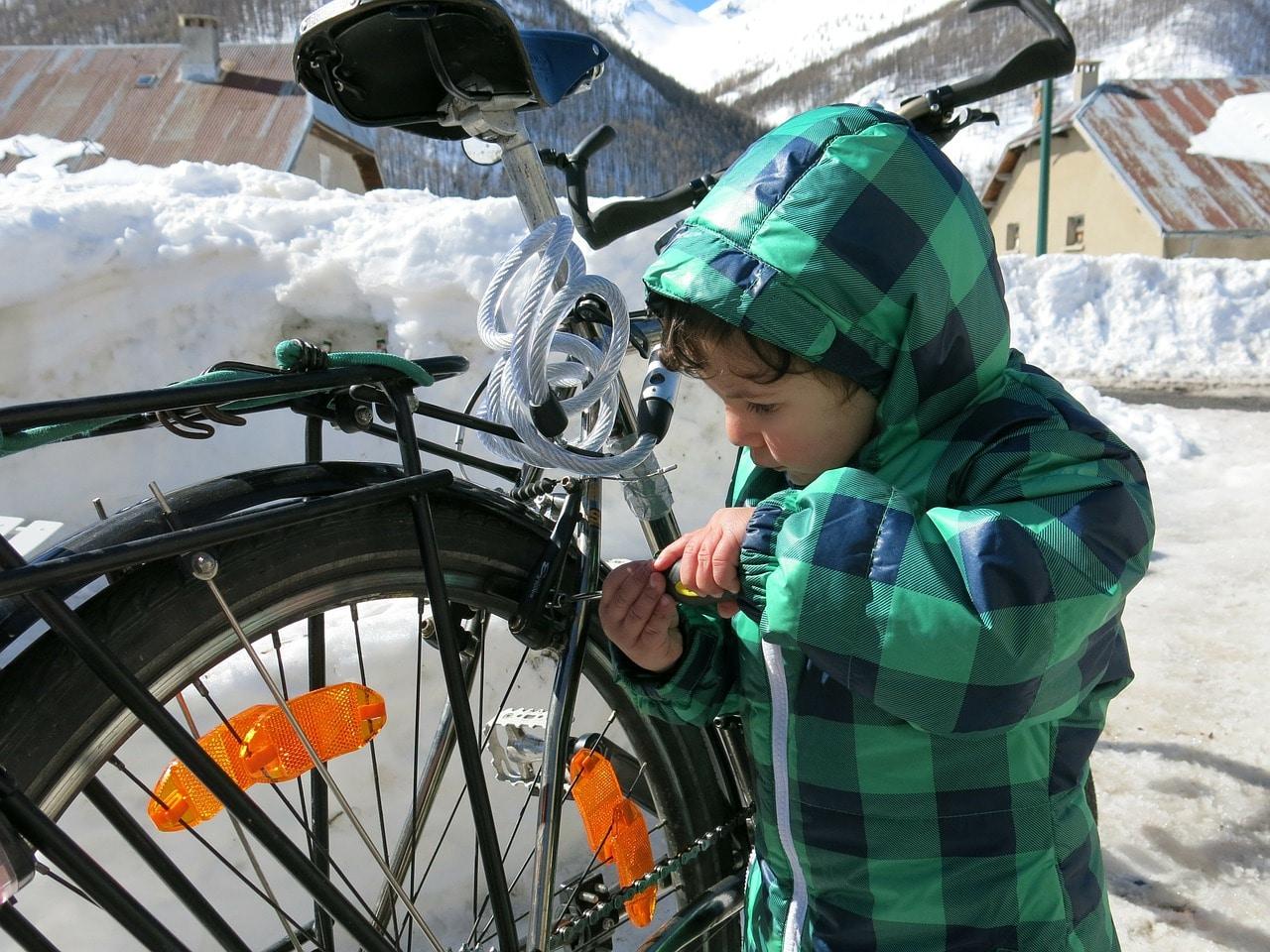 Na zdjęciu: małe dziecko sprawdza stan klocków hamulcowych