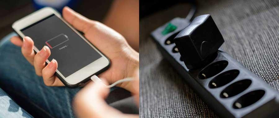 Ładowarka do telefonu w listwie i rozładowany telefon