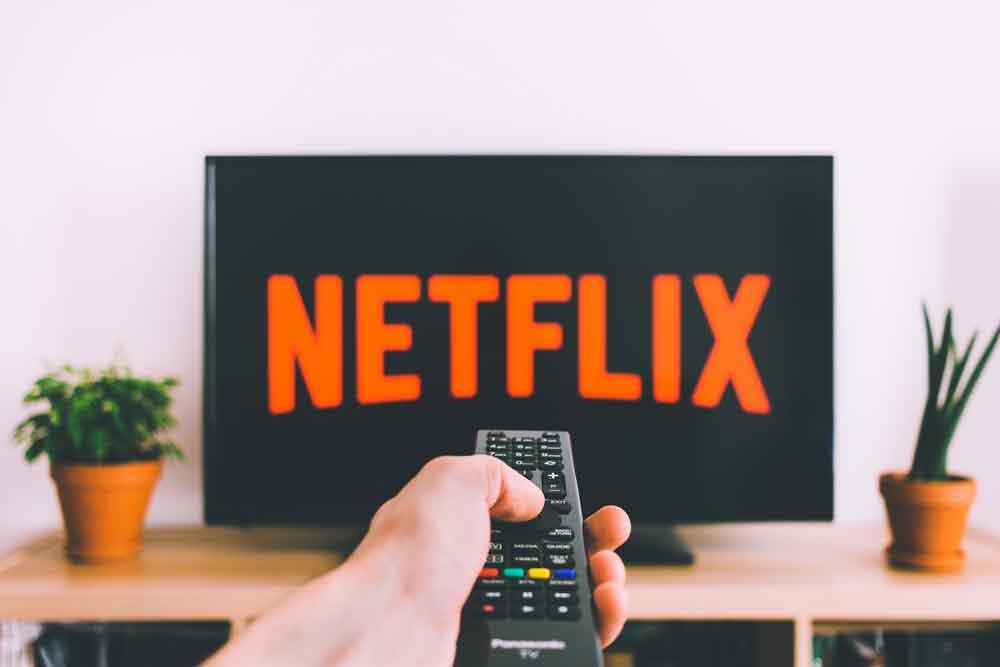 Netflix - ilustracja. Pilot do telewizora włącza Netflix na telewizorze