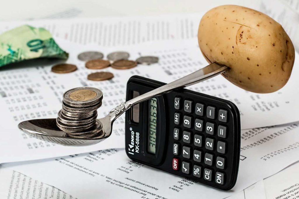 Inflacja - ilustracja. Ziemniak przeważający pieniądze na wadze z łyżki i kalkulatora
