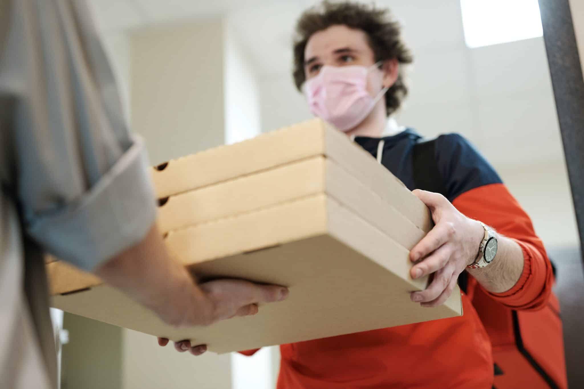 Na zdjęciu dostawa jedzenia - dostawca wręcza zamówione jedzenie